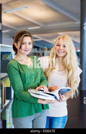 Portrait of high school female friends with books in library - Stock Photo