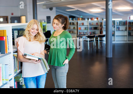 Female high school students reading book in school library - Stock Photo