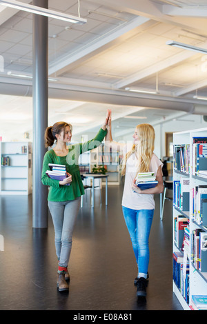 Full length of female students giving high-five in school library - Stock Photo