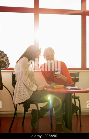 Happy teenage girls using mobile phone at school cafe - Stock Photo