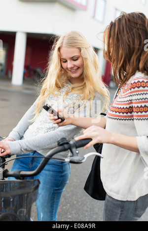 Happy teenage girls with bicycle using mobile phone on high school campus - Stock Photo
