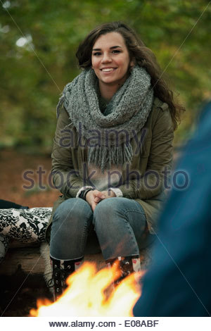 Portrait of happy young woman camping in forest - Stock Photo