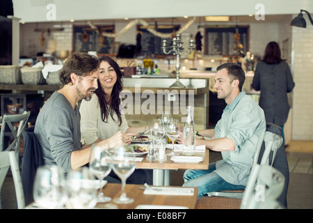 Happy friends discussing at restaurant table - Stock Photo