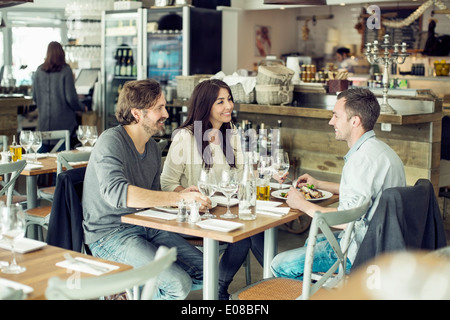 Happy friends discussing at table in restaurant - Stock Photo