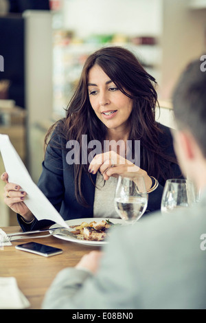 Businesswoman discussing with male colleague at restaurant table - Stock Photo
