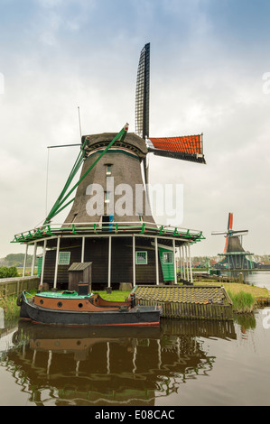 DUTCH WINDMILLS WITH ORANGE SAILS AND A BOAT ON THE CANAL AT ZAANSE SCHANS HOLLAND - Stock Photo