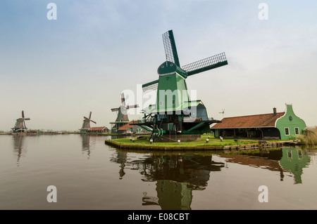 FOUR DUTCH WINDMILLS AND THE CANAL AT ZAANSE SCHANS NETHERLANDS IN SPRINGTIME - Stock Photo