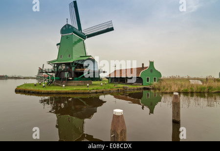 GREEN WINDMILL AND OLD  HOUSE ON THE CANAL AT ZAANSE SCHANS HOLLAND IN SPRINGTIME - Stock Photo