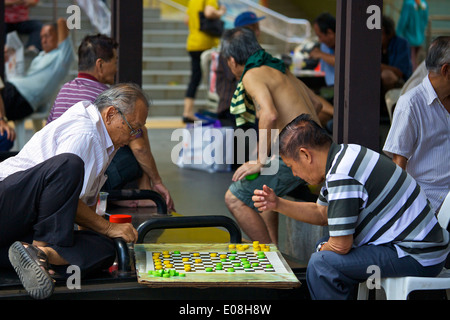 Group Of Asian Seniors Playing Checkers on Sago Lane, Singapore. - Stock Photo