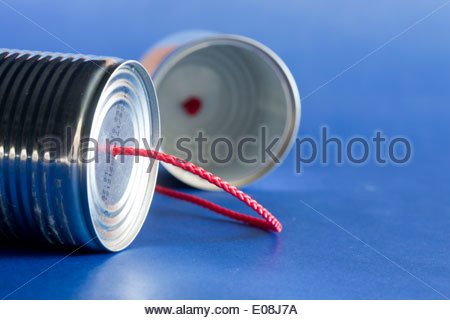 Tin can telephone with a red string - Stock Photo