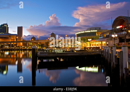 Dawn breaks over a stormy sky in Darling Harbour, Sydney, Australia. - Stock Photo