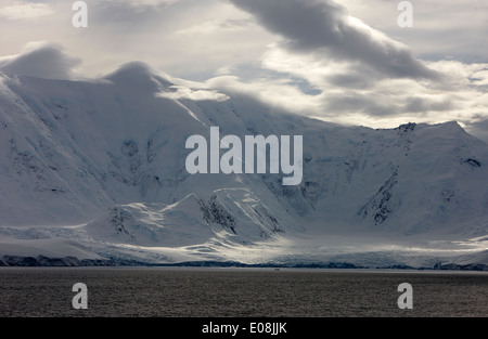 sunlight breaking through clouds on snow covered landscape of anvers island and neumayer channel Antarctica - Stock Photo