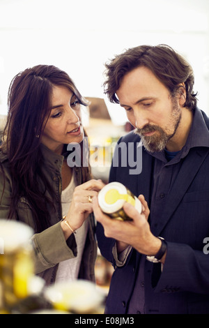 Mature couple reading product label in supermarket - Stock Photo