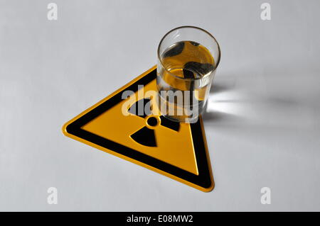 Illustration - A glass of water stands on a radioactive trefoil sign in Germany, 03 April 2011. Photo: Berliner - Stock Photo