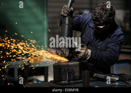 Factory worker using angle grinder to cut metal - Stock Photo