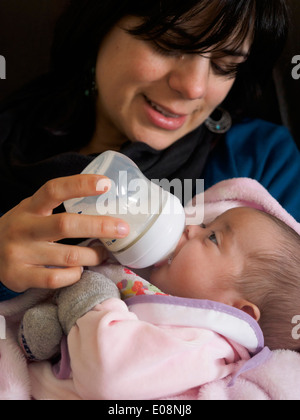 Young mother bottle feeding her newborn baby - Stock Photo