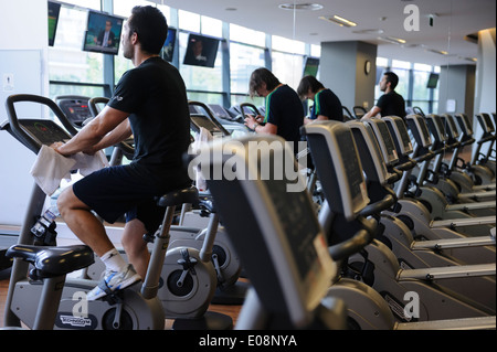 People working out on exercise bike at the gym - Stock Photo