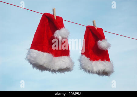 Illustration - Two Santa hats hang on a clothesline in Germany, 28 December 2009. Photo: Berliner Verlag/Steinach - Stock Photo