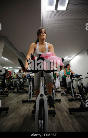 Young woman riding stationary bicycle during a spinning class at the gym - Stock Photo
