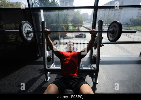 Man lifting weights at the gym - Stock Photo