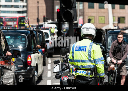 London, UK. 6th May 2014, A Metropolitan Motorcycle officer watches helplessly as taxis jam the streets of Southwark - Stock Photo