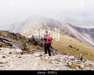 Walker walking down Rhyd Ddu path from Mt Snowdon with low cloud creating hill fog in Snowdonia National Park. Gwynedd - Stock Photo