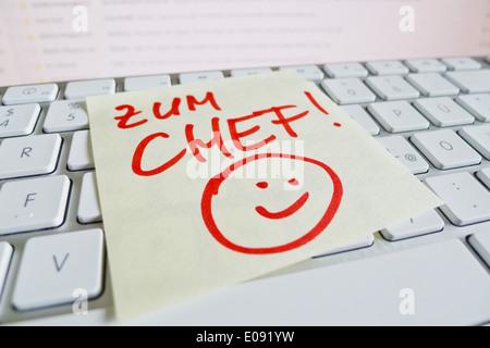 A note slip of paper lies on the keyboard of a computer in memory: To the boss, Ein Notizzettel liegt auf der Tastatur - Stock Photo