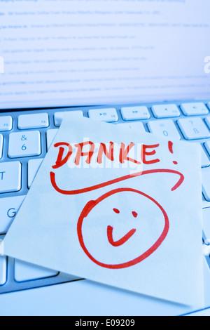 A note slip of paper lies on the keyboard of a computer in memory: Thanks, Ein Notizzettel liegt auf der Tastatur - Stock Photo