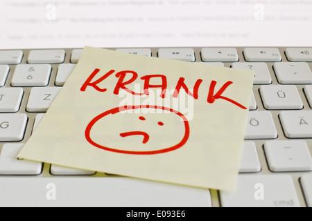 A note slip of paper lies on the keyboard of a computer in memory: Ill, Ein Notizzettel liegt auf der Tastatur eines - Stock Photo