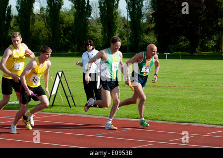 Athletics, runners passing baton in men`s 4X400m relay race at club level, UK - Stock Photo