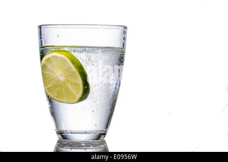 A glass with fresh drinking water and a lime. Mineral water as a Durstloescher., Ein Glas mit frischem Trinkwasser - Stock Photo