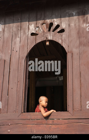 South East Asia Myanmar Burma Shan State Nyaungshwe also known as Nyaung Shwe young Buddhist monk in window at Shwe - Stock Photo