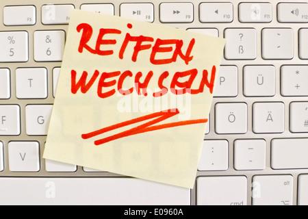 A note slip of paper lies on the keyboard of a computer in memory: Tyres change, Ein Notizzettel liegt auf der Tastatur - Stock Photo