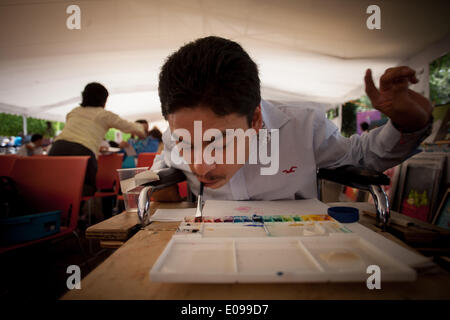 Mexico City, Mexico. 6th May, 2014. A man with disabilities paints with his mouth during the 4th Fair of Rights - Stock Photo