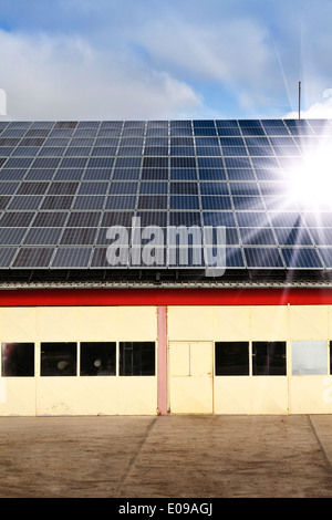 Using renewable solar energy with solar panels on the roof - Stock Photo