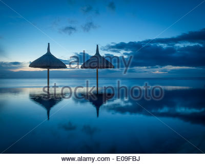 Mauritius, La Preneuse, two sunshades at swimming pool in front of the sea - Stock Photo