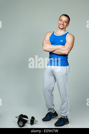 Full-length portrait of a muscular man standing with arms folded on gray background - Stock Photo
