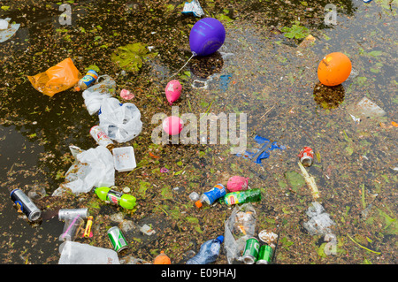 DEBRIS BOTTLES CANS BALLOONS AND OTHER LITTER FLOATING IN A CANAL IN DELFT HOLLAND Stock Photo