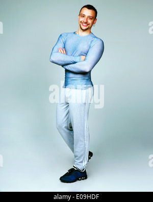 Full-length portrait of a happy man standing with arms folded on gray background - Stock Photo