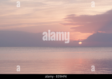Sun sets over calm sea with soft pink pastel shades - Stock Photo