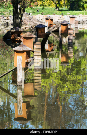 Boxes for waterfowl nesting are mirrored in the water. Natural theme. - Stock Photo