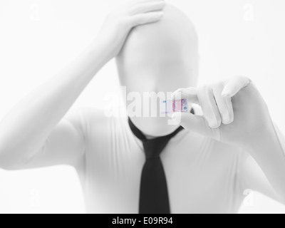 Unknown worried person dressed in white suit with black tie holding a small euro bill - Stock Photo