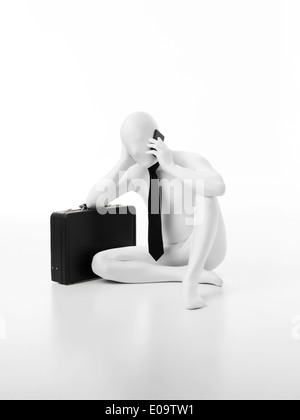 Faceless businessman dressed in white leaning on black briefcase, talking on the phone - Stock Photo