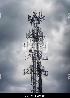 Mobile phone antenna tower against a dark stormy sky - Stock Photo