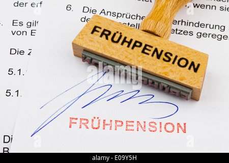 A stamp of wood lies on a document. German label: Early pension, Ein Stempel aus Holz liegt auf einem Dokument. - Stock Photo
