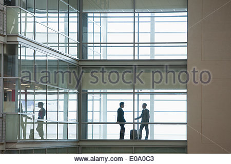 Businessmen walking along corridor in modern office - Stock Photo