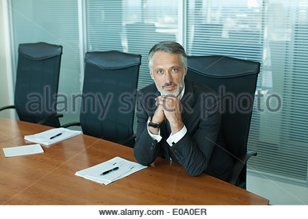 Portrait of confident businessman with hands clasped - Stock Photo
