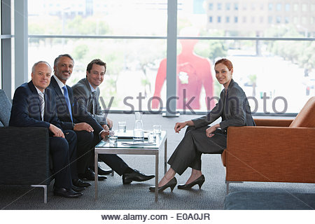 Businesswoman leading meeting with co-workers in lobby - Stock Photo