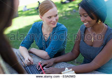 Businesswomen working on laptop in park - Stock Photo
