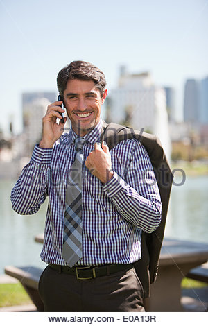 Businessman talking on cell phone outdoors - Stock Photo